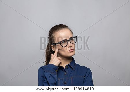 Portrait of puzzled woman in glasses on gray background
