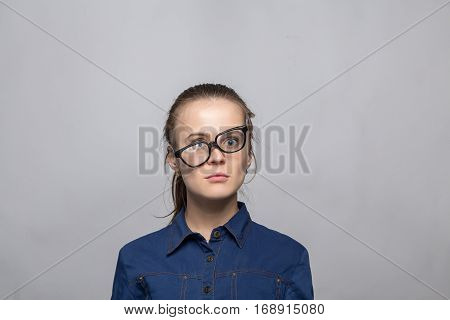 Portrait of remembered woman in glasses on gray background