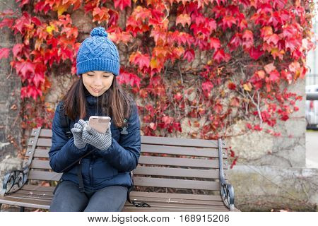 Woman using cellphone and sitting down on bench