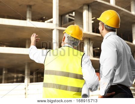 Engineer and worker discussing construction of unfinished building
