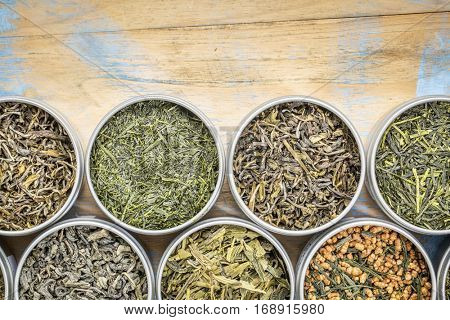 green tea sampler - top view of loose leaf teas in tins against grunge wood with a copy space