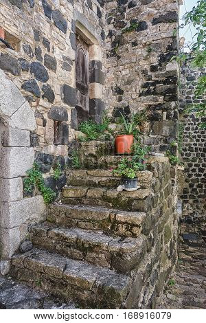 Old staircase in front of the door decorated with plants in flower pots in the picturesque village of Mirabel in the Ardèche region of France.