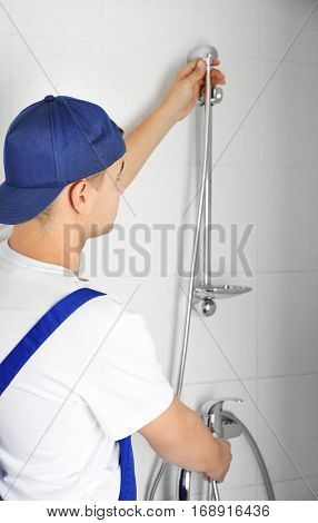 Young handsome plumber fixing shower indoors