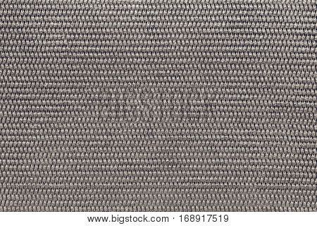 the abstract textured background of gray brown color of polymeric material or synthetic fabric with a corrugated symmetric pattern and with small droplets of water