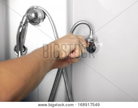 Young plumber fixing hose in shower cabin