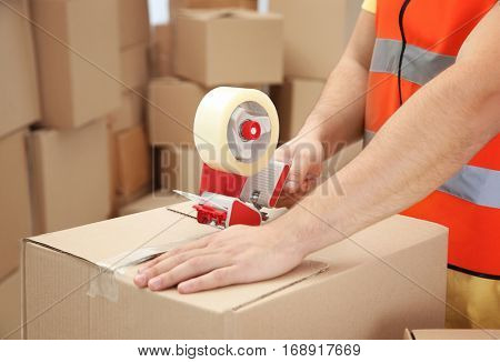 Closeup of man packing parcels with sticky tape at warehouse