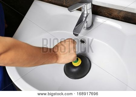 Plumber cleaning sink with plunger in bathroom