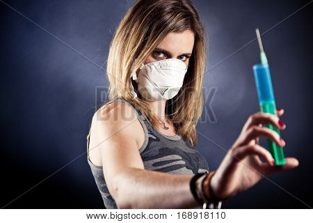young woman with flu mask, holding a syringe. selective focus on her face, syringe is out of focus.