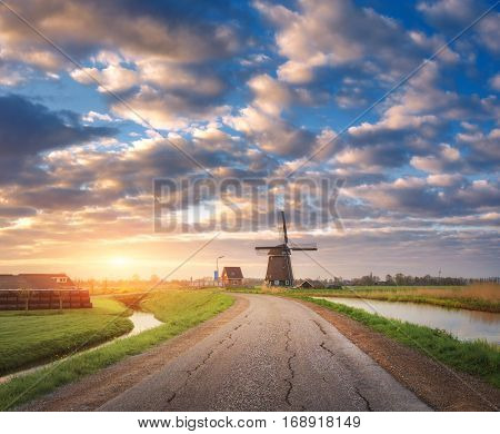 Traditional Dutch Windmill Against Colorful Sky With Clouds