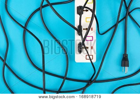 Maximum electrical cords connected electrical power strip or extension block with messy wires top view on colorful background messy electric equipment flat lay concept.