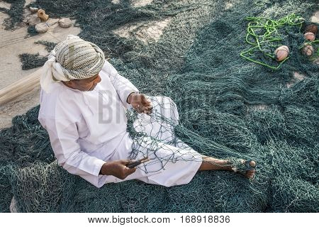 Muscat Oman February 4th 2017: old omani man repairing a fish net