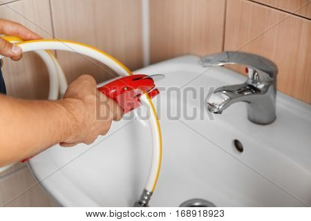 Plumber cutting water flexible hose in bathroom close up