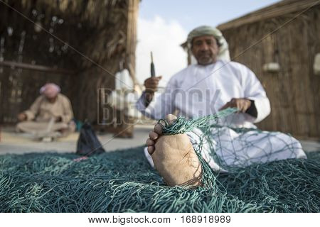 Muscat Oman February 4th 2017: cracked foot of an old omani man repairing a fish net