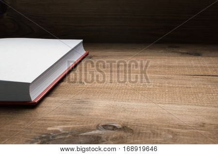 Open book on the wooden table. White page.