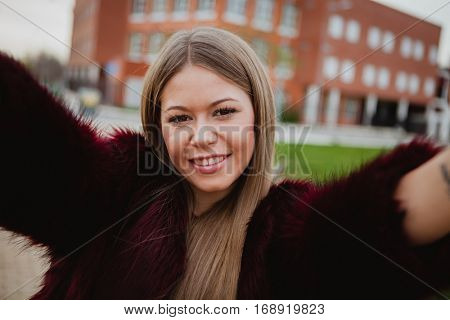 Pretty blonde girl with fur coat in the park making herself a photo