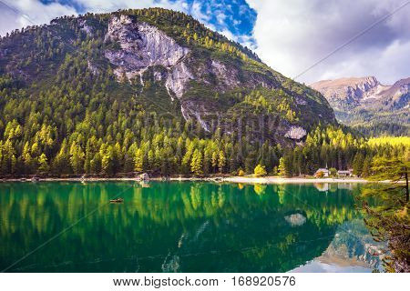 Magnificent lake Lago di Braies. Emerald expanse of water reflects the surrounding forest and mountains. The concept of walking and eco-tourism. South Tyrol, Italy