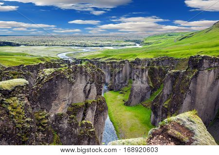 Green Tundra in July. The striking canyon in Iceland. The concept of active northern tourism. Bizarre shape of cliffs surround the stream with glacial water