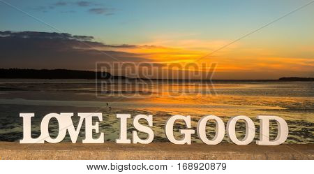 3D words saying 'love is good' as the sun goes down into clouds over a river lagoon.