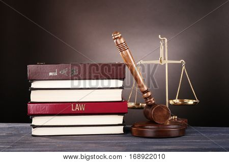 Judge gavel, scales and books on wooden table
