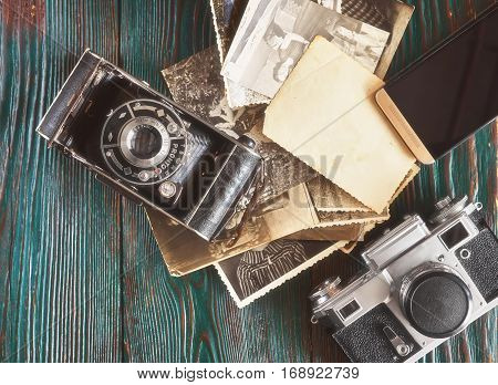 Three Generations Of A Photo Cameras And Old Photos On Memory. Ancient Authentic Wooden Background
