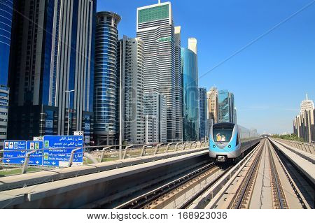 DUBAI UAE - JANUARY 27: Dubai automated metro railways and train view with skyscrapers of Downtown Dubai on January 27 2017 Dubai UAE.