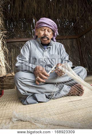 Muscat Oman February 4th 2017: old oman man making a fish net