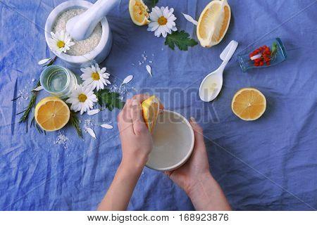 Female hands squeezing lemon juice into bowl, top view