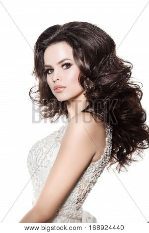 Side view of pretty brunette woman wearing white wedding dress turned away posing and looking at camera. Girl with long wavy hair plump lips and stylish haircut and evening make up. Studio isolate.