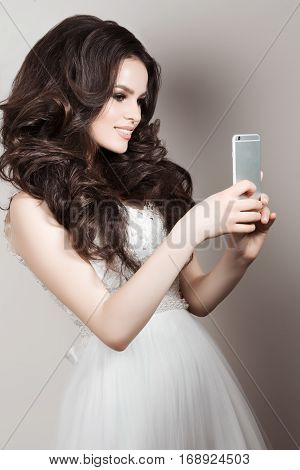 Pretty smiling bride in wedding dress posing when tacking photo herserself on smart phone. Brunette girl with long curly hair and perfect make up taking selfie on her call phone. White background.