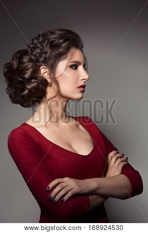 Portrait of confident brunette girl posing with crossed arms turned away. Beautiful woman wearing red dress with big neckline perfect haircut evening make up and violet manicure. Gray background.