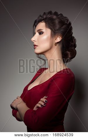 Side view of attractive and confident brunette woman wearing red dress with big neckline turn away and posing with crossed hands. Model with perfect haircut evening make up. Gray studio background.