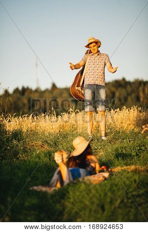 Man standing looking away and searching her girlfriend. Brunette woman with long hair wearing dress hiding and lying on grass. Couple wearing in hats. Hot sunny summer day.