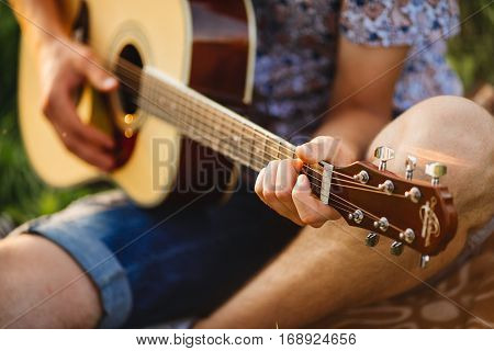 Crop of incognito male hand playing on guitar. Man sitting on grass and creating song with music instrument. Romantic atmosphere outdoor. Male wearing jeans shorts and checked shirt.