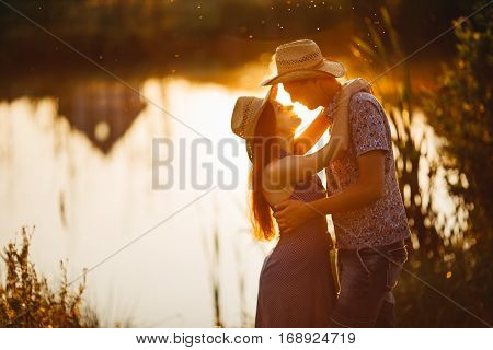 Couple of brunette woman and man in hat embracing sensuality looking each other. Girlfriend and boyfriend standing on pier of river at sunset. Woman wearing dress man in shirt. Warm colors.