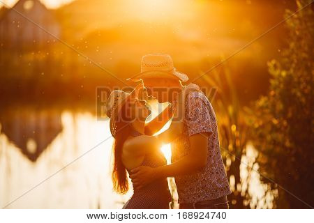 Portrait of couple of brunette woman and man standing on pier of lake at sunset embracing and smiling. Girlfriend and boyfriend sensuality looking each other. Girl in dress man in shirt and hat.