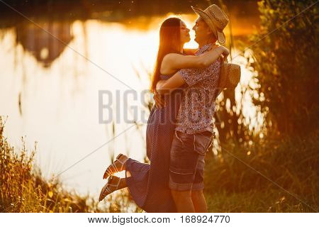 Courageous man in hat holding his brunette wife on hand smiling and looking each other. Romantic atmosphere on pier of lake at sunset. Couple standing face to face laughing and enjoying. Summertime.