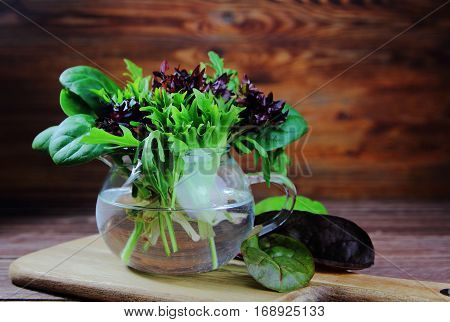 Mixed salad leaves in a glass jug on the table