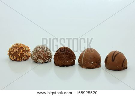 Various chocolates in a row bonbons with different topping and filling