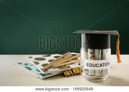 School supplies and glass jar with money for education on wooden table against green background