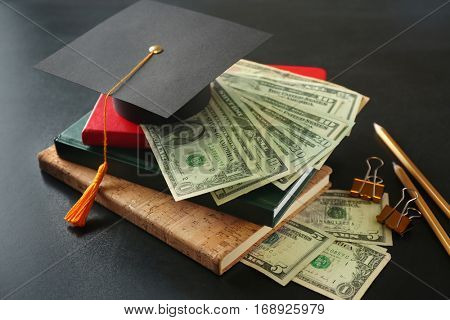 School supplies, graduation hat and dollar banknotes on blackboard. Pocket money concept
