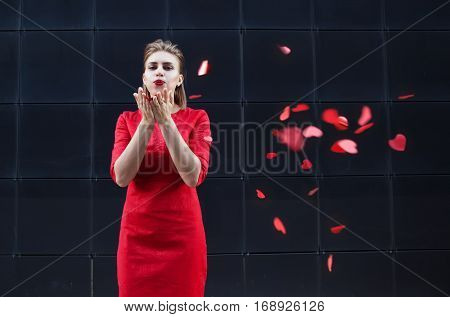 Valentine's Day concept, woman in red dress blowing on a paper heart, on a dark background.