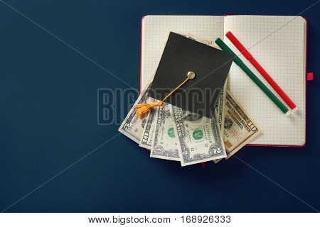 School supplies, graduation hat and banknotes on green background. Pocket money concept