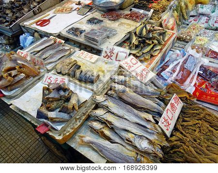 North Point, Hong Kong - February 13, 2016: Booth with various seafood on the Java Road Market in North Point, Hong Kong. At the stall of fresh, smoked, dried and packaged seafood is offered. The goods are marked with large price tags.