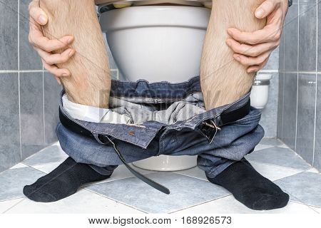 Legs of man with diarrhea who is sitting on toilet.