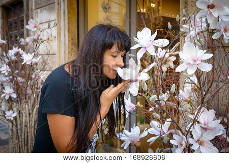 Nice girl sniffing big white flower in a Rome street