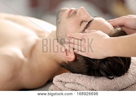 Man having face massage in spa salon