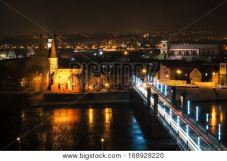 View from above of Vytautas the Great Church of the Assumption of The Holy Virgin Mary and Vilnius University Kaunas Faculty of Humanities in the Old Town Vytautas the Great Bridge Aleksotas over Nemunas river at night Kaunas Lithuania