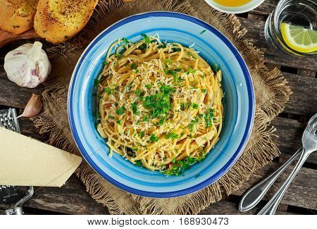 Vegetarian Italian Pasta Spaghetti Aglio E Olio with garlic bread, red chili flake, parsley, parmesan cheese and glas of water.