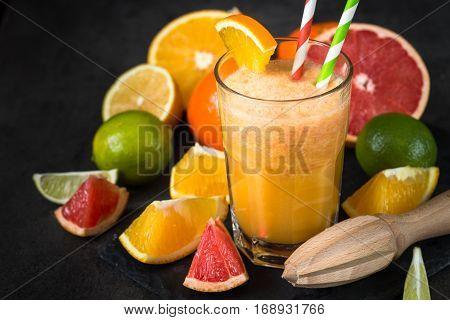 Citrus drink. Fresh citrus smoothie juice at dark background.