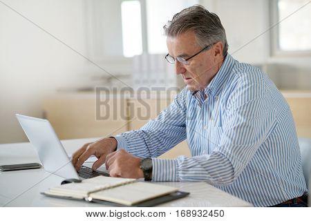 Senior man in office working on laptop computer